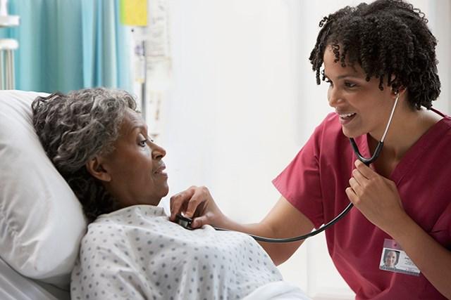 A clinician checks a patient's heartbeat.
